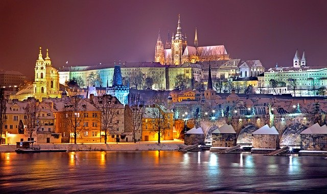 Vista nocturna de Praga con el puente San Carlos a la derecha